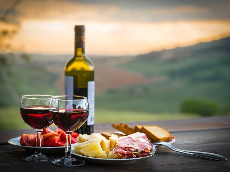 Wine and cheese with vineyard in background